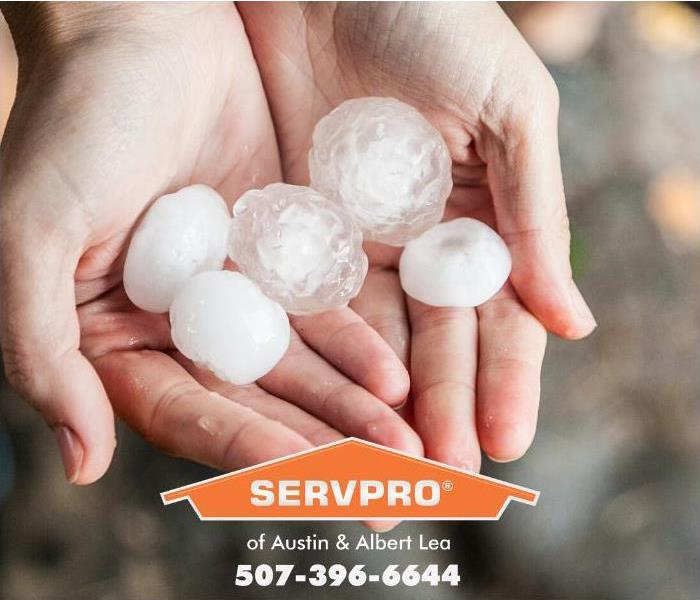 A person is shown holding a handful of large hailstones.