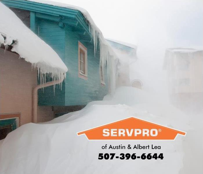 Homes are shown bombarded with heavy snow on a winter day.